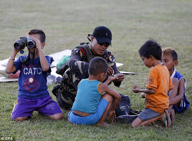 0578-2906730-epa04556758_A_Filipino_soldier_plays_with_children_as_security_f-a-19_1421135531634.jpg